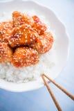 Пряный сладостный и кислый цыпленок с сезамом и рисом на голубой деревянной предпосылке Стоковое фото RF