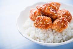 Пряный сладостный и кислый цыпленок с сезамом и рисом на голубой деревянной предпосылке Стоковые Фотографии RF