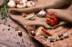 Пряный чеснок, прозрачный банк горячих красных перцев, яичка триперсток и розмариновое масло на скомканной бумажной и деревянной  Стоковое Изображение