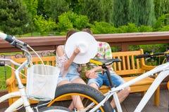 Прятать мальчика и девушки целуя за шляпой пока сидящ на быть Стоковое Изображение