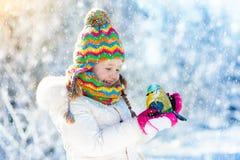 Птица ребенка подавая в парке зимы Игра детей в снеге природа и Стоковые Фотографии RF