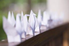 Птицы белой бумаги Origami в ряд на фокусе балкона выборочном стоковые фото