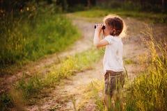 Птицы девушки ребенка наблюдая с бинокулярным на прогулке в лесе лета Стоковая Фотография