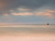 Птицы моря на валуне вставляя вне от ровного волнистого моря Выравнивать волнистый океан Темный горизонт с последними лучами солн стоковое фото rf