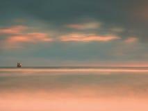 Птицы моря на валуне вставляя вне от ровного волнистого моря Выравнивать волнистый океан Темный горизонт с последними лучами солн Стоковое Изображение
