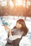 Птицы молодой женщины и зимы в женщине зимы клетки на backgroun Стоковые Фото