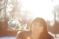 Птицы молодой женщины и зимы в клетке Стоковое Фото