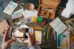Публикация фото с произведением искусства на интернете Рука держит телефон и фотографирует произведение искусства Столешница стол стоковая фотография