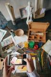 Публикация фото с произведением искусства на интернете Рука держит телефон и фотографирует произведение искусства Столешница стол стоковая фотография rf