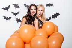 Пугающие женщины при состав хеллоуина держа воздушные шары и показывая зубы Стоковое фото RF