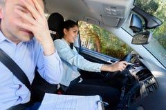 Пугающий инструктор по вождению с женским водителем учащийся стоковое фото