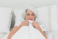 Пугливая женщина схватывая ее лоскутное одеяло Стоковая Фотография RF