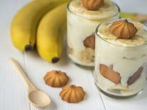 Пудинг банана в стеклах с печеньями на белой деревянной винтажной таблице Стоковое Фото