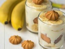 Пудинг банана в стеклах с печеньями на белом деревянном столе Стоковые Изображения