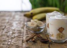 Пудинг банана с сливк, печеньями и циннамоном на винтажной таблице Стоковые Фотографии RF
