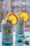 Пудинг молока банана с chia и апельсин в опарниках стекла украшенных с 2 ложками с сырцовыми семенами chia на голубой деревянной  Стоковое Фото