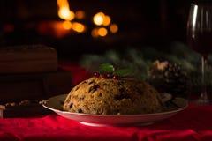 Пудинг рождества и свет рождества на деревянном столе Стоковые Фото