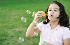 Пузыри девушки дуя напольные Стоковые Фото