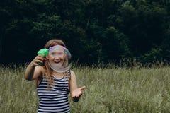 Пузыри девушки дуя с оружием пузыря стоковые фото
