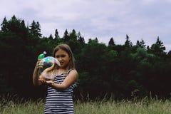 Пузыри девушки дуя с оружием пузыря стоковое изображение rf