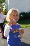 Пузыри дуновений маленькой девочки стоковая фотография
