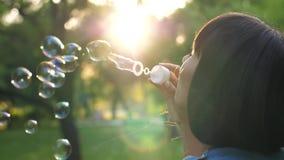 Пузыри дуновения женщины на заходе солнца видеоматериал