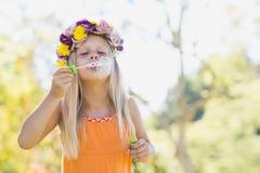 Пузыри маленькой девочки дуя через палочку пузыря Стоковое Фото