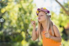 Пузыри маленькой девочки дуя через палочку пузыря Стоковая Фотография RF