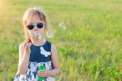 Пузыри милой девушки дуя в парке, открытом космосе Стоковое фото RF