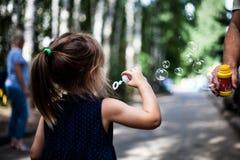Пузыри милой девушки дуя в парке Стоковые Фото