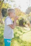 Пузыри молодого мальчика дуя через палочку пузыря Стоковые Изображения