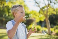 Пузыри молодого мальчика дуя через палочку пузыря Стоковое Фото