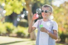 Пузыри молодого мальчика дуя через палочку пузыря Стоковая Фотография RF