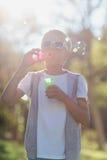 Пузыри молодого мальчика дуя через палочку пузыря Стоковое Изображение