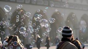 Пузыри молодого человека дуя, счастливые туристы и дети играя с ними сток-видео