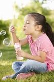 Пузыри молодой испанской девушки дуя в парке Стоковые Фотографии RF