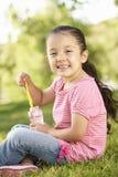Пузыри молодой испанской девушки дуя в парке Стоковая Фотография