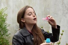 Пузыри мыла девочка-подростка дуя стоковое фото rf