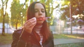 Пузыри мыла женщины дуя внешние Предназначенная для подростков девушка имея потеху в парке - дуя пузыри мыла видеоматериал
