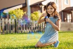 Пузыри мыла милой девушки дуя в задворк Стоковая Фотография RF