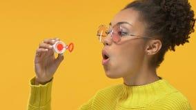 Пузыри мыла радостной чернокожей женщины дуя на желтой предпосылке, счастье молодости акции видеоматериалы