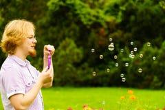 Пузыри мыла человека дуя внешние стоковое изображение