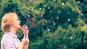 Пузыри мыла человека дуя внешние стоковые изображения rf
