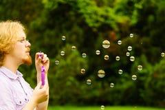 Пузыри мыла человека дуя внешние стоковое фото rf