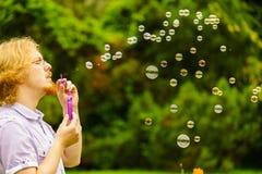 Пузыри мыла человека дуя внешние стоковые фотографии rf