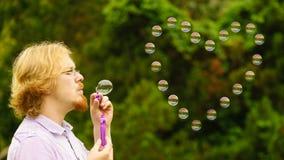 Пузыри мыла человека дуя внешние стоковая фотография