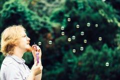 Пузыри мыла человека дуя внешние стоковое фото