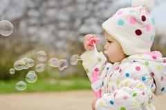 Пузыри мыла девушки малыша дуя Стоковое Изображение RF