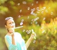 Пузыри мыла девушки дуя в sunlit парке Стоковое Изображение