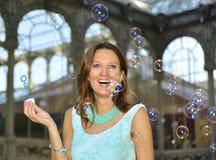 Пузыри мыла девушки дуя к воздуху outdoors в концепции очарования и потехи Стоковые Изображения RF